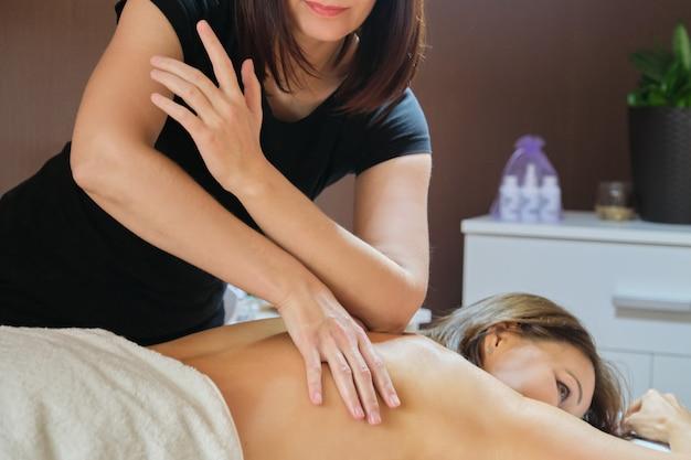 Mulher madura, deitado na mesa de massagem e recebendo massagem médica nas costas