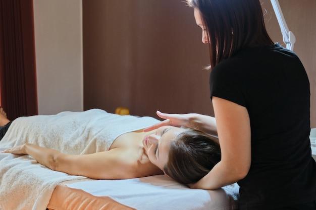 Mulher madura, deitado na mesa de massagem e recebendo massagem médica
