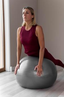 Mulher madura dentro de casa usando uma bola prateada de fitness