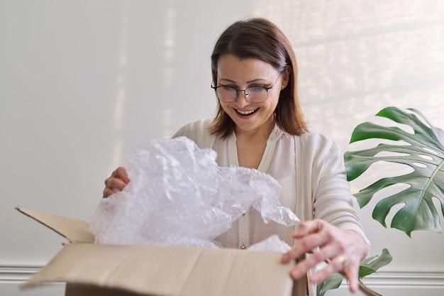 Mulher madura desempacota a caixa de papelão na mesa em casa, no escritório