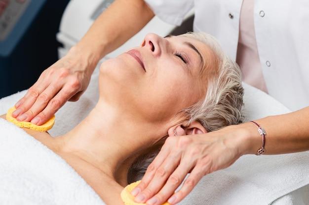 Mulher madura, desfrutando da terapia de rejuvenescimento da pele no centro de cosmetologia.
