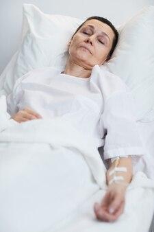 Mulher madura doente deitada na cama no hospital