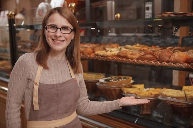 Mulher madura e alegre gostando de trabalhar em sua padaria, apontando com orgulho para uma vitrine de varejo