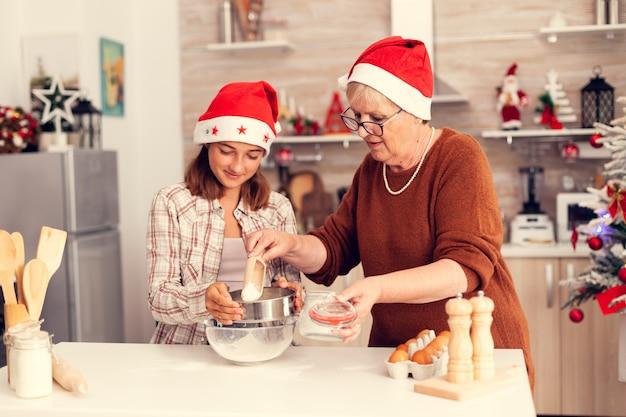 Mulher madura e criança no dia de natal fazendo massa de biscoitos