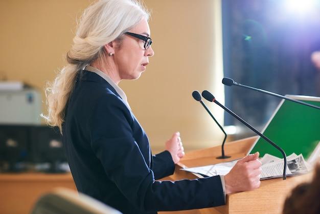 Mulher madura e elegante delegada em terno falando no microfone enquanto ficava ao lado da tribuna na sala de conferências no cume