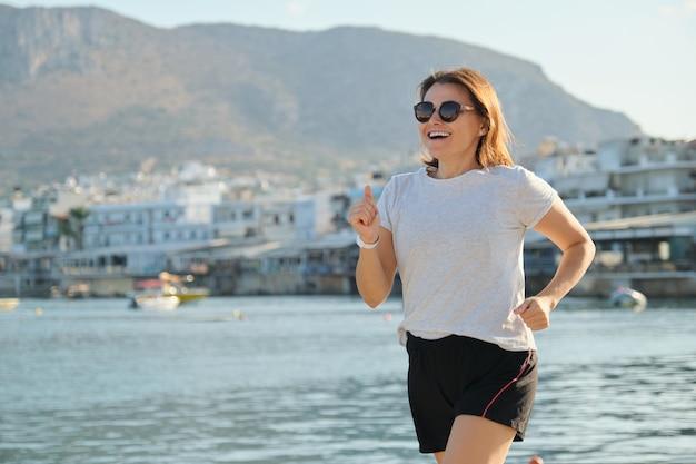 Mulher madura e esportiva sorridente correndo no calçadão