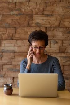 Mulher madura e feliz sorrindo enquanto fala no celular e usa o laptop na mesa de madeira contra a parede de tijolos