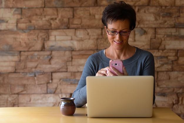 Mulher madura e feliz sorrindo enquanto usa o telefone celular com o laptop na mesa de madeira contra a parede de tijolos