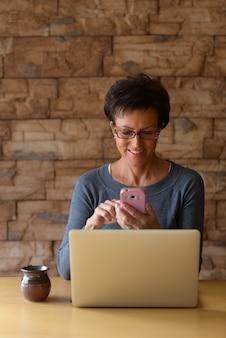 Mulher madura e feliz sorrindo enquanto usa o telefone celular com o laptop na mesa de madeira contra a parede de tijolos Foto Premium