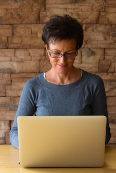 Mulher madura e feliz sorrindo enquanto usa óculos e usa o laptop na mesa de madeira contra a parede de tijolos Foto Premium