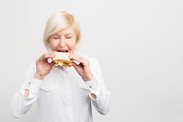 Mulher madura e satisfeita está comendo seu sanduíche caseiro com prazer. ela está pronta para dar uma primeira mordida nesta refeição.