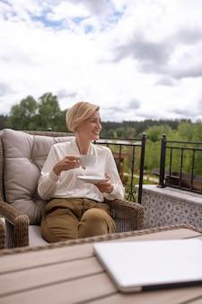 Mulher madura elegante e animada com uma xícara e um pires nas mãos e olhando para longe