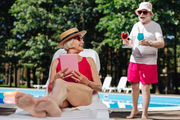 Mulher madura elegante usando chapéu de palha, tomando banho de sol perto da piscina e lendo livro eletrônico
