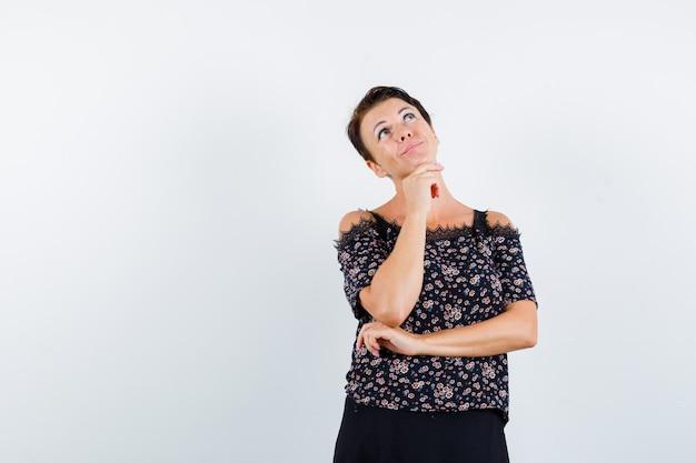 Mulher madura em blusa floral e saia preta apoiando o queixo na mão, pensando em algo e parecendo pensativa, vista frontal.