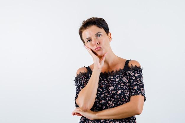 Mulher madura em blusa floral e saia preta, inclinando a bochecha na palma da mão, pensando em algo e olhando pensativa, vista frontal.
