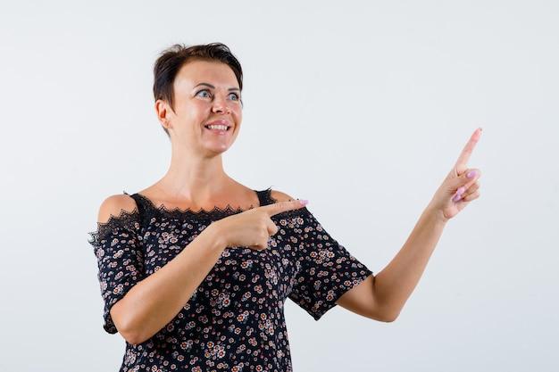 Mulher madura em blusa floral, saia preta apontando para a direita e para cima com o dedo indicador, olhando para cima e parecendo alegre, vista frontal.