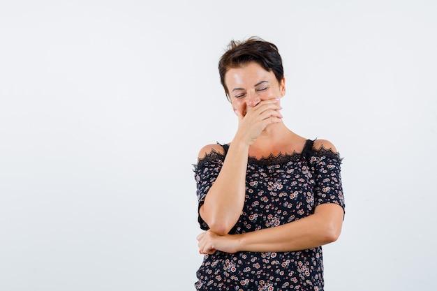 Mulher madura em blusa floral, saia preta cobrindo a boca com a mão, rindo e olhando alegre, vista frontal. Foto gratuita