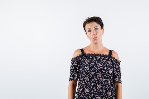 Mulher madura em blusa floral, saia preta curvando os lábios e olhando séria, vista frontal.