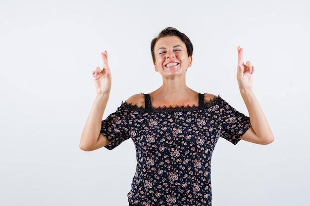 Mulher madura em blusa floral, saia preta mantendo os dedos cruzados, sorrindo e olhando alegre, vista frontal.