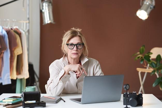Mulher madura em óculos, sentada à mesa em frente ao anúncio de laptop, olhando para a câmera enquanto trabalha em um depósito
