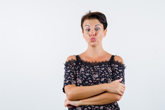 Mulher madura em pé com os braços cruzados, curvando os lábios, fazendo estrabismo para se divertir em uma blusa floral, saia preta e parecendo divertido. vista frontal.