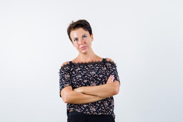 Mulher madura em pé com os braços cruzados na blusa e parecendo confiante. vista frontal.