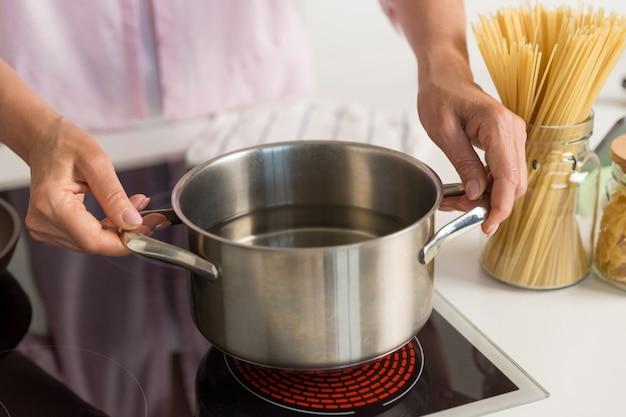 Mulher madura em pé na cozinha cozinhando.