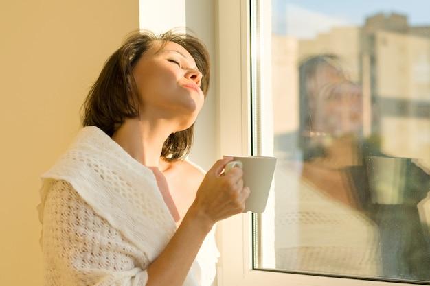 Mulher madura em pé perto da janela com copo