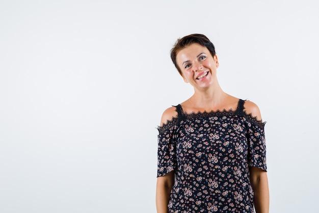 Mulher madura em pé, sorrindo em blusa floral, saia preta e olhando alegre, vista frontal.