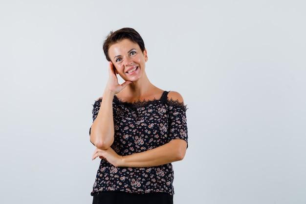 Mulher madura em pose de pensamento de blusa de pé e parecendo alegre. vista frontal.