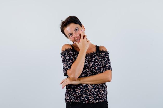 Mulher madura em pose de pensamento enquanto sorri na blusa e parece atraente. vista frontal.