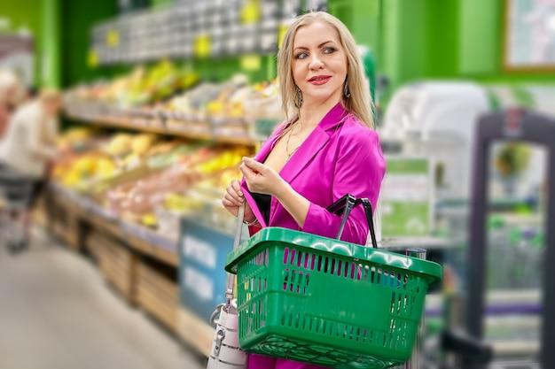 Mulher madura em rosa dentro do supermercado com uma cesta de compras verde.
