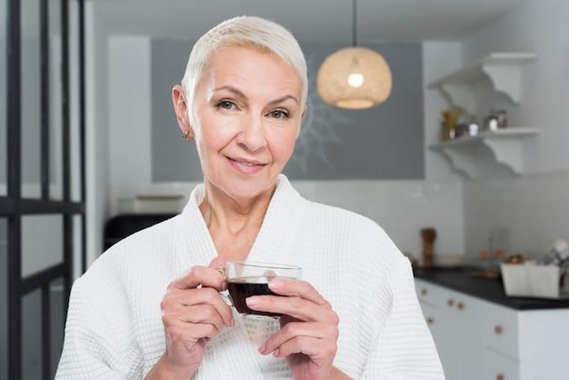 Mulher madura em roupão posando na cozinha, mantendo a xícara de café