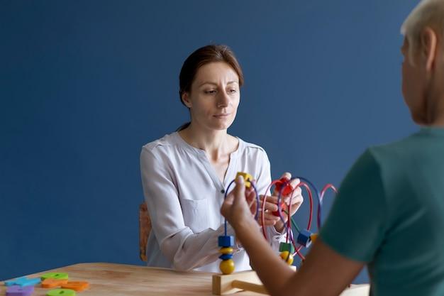 Mulher madura em sessão de terapia ocupacional com psicóloga