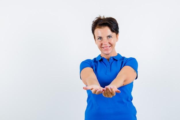 Mulher madura em t-shirt azul, mantendo as mãos em concha estendidas e parecendo gentil, vista frontal.