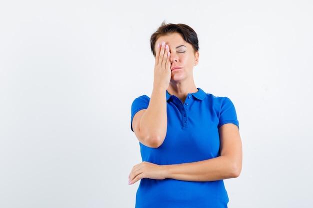 Mulher madura em t-shirt azul, segurando a mão no olho e olhando pensativa, vista frontal.