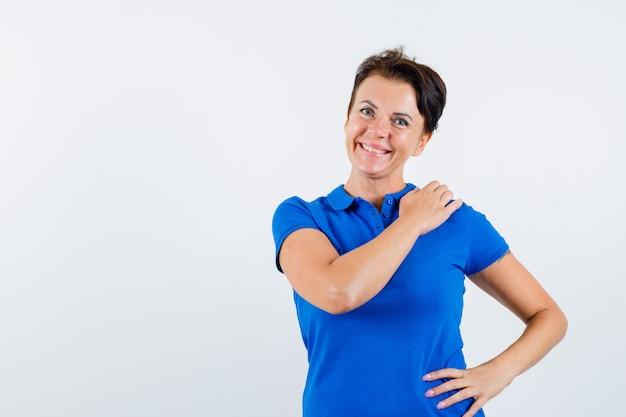 Mulher madura em t-shirt azul, segurando a mão no ombro e olhando feliz, vista frontal.