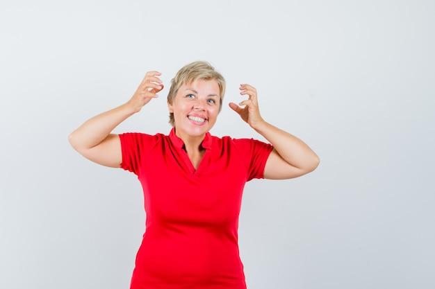 Mulher madura em t-shirt vermelha fingindo tirar os fones de ouvido e olhando feliz.