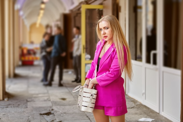 Mulher madura em um terno rosa está procurando algo em sua bolsa.
