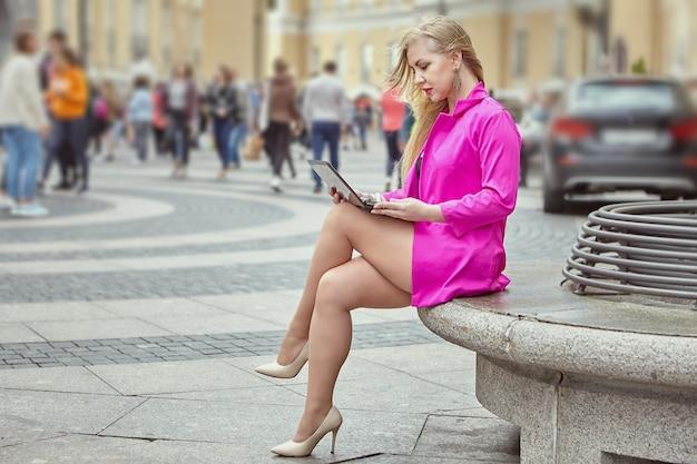Mulher madura em um terno rosa está sentada com o notebook de joelhos na rua movimentada da cidade.