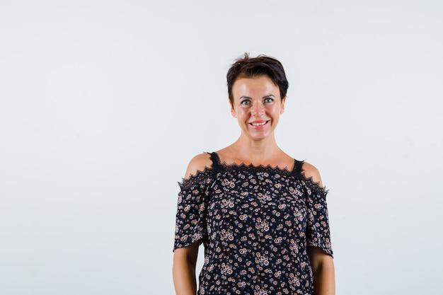 Mulher madura em uma blusa floral, saia preta em pé em linha reta e posando para a câmera e olhando alegre, vista frontal.