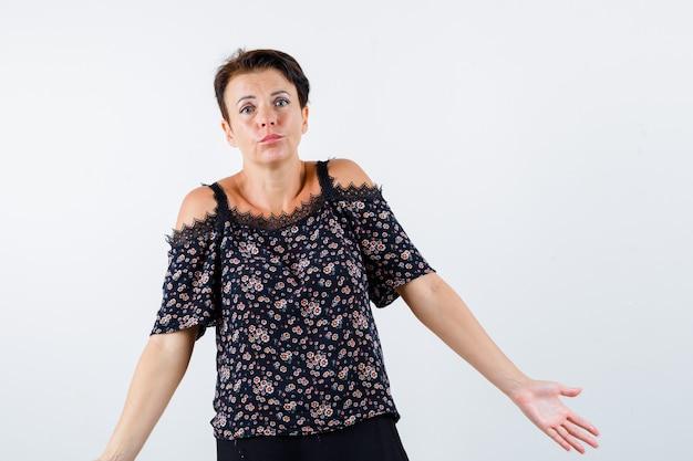 Mulher madura em uma blusa floral, saia preta, mostrando um gesto de impotência e parecendo perplexa, vista frontal.