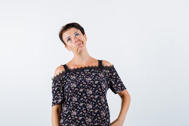 Mulher madura em uma blusa floral, saia preta segurando a mão na cintura, curvando os lábios, olhando para longe e olhando pensativa, vista frontal.