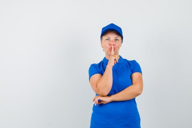 Mulher madura em uma camiseta azul mostrando gesto de silêncio e olhando com cuidado