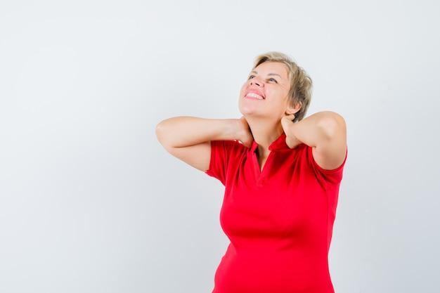 Mulher madura em uma camiseta vermelha, sofrendo de dor no pescoço e parecendo cansada