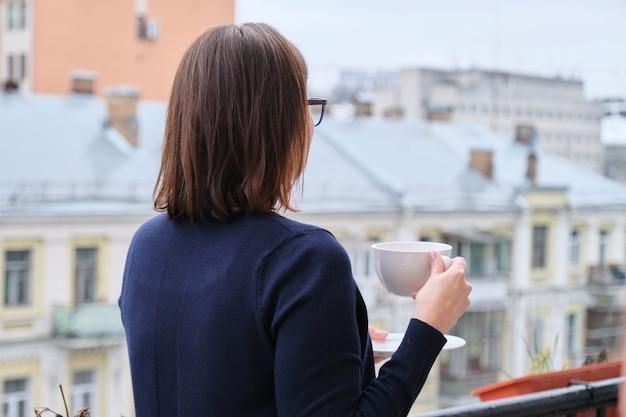 Mulher madura em uma varanda aberta com uma xícara de chá, mulher olha para a cidade enquanto está isolada, em quarentena durante a infecção viral, copie o espaço