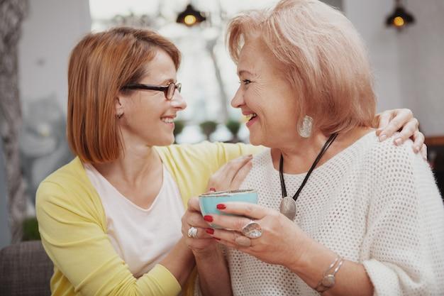 Mulher madura, encontrar sua mãe sênior na cafeteria