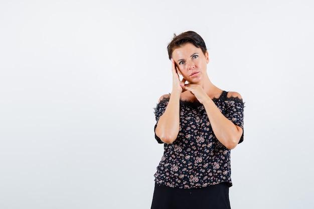 Mulher madura, encostando a bochecha na palma da mão em uma blusa floral e saia preta e está linda. vista frontal.