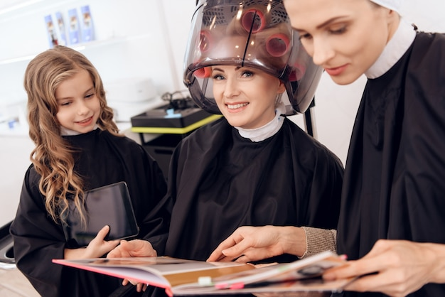 Mulher madura escolhe penteado no catálogo.