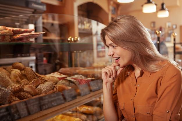 Mulher madura, escolhendo deliciosos bolos a partir do visor na loja de padaria, cópia espaço